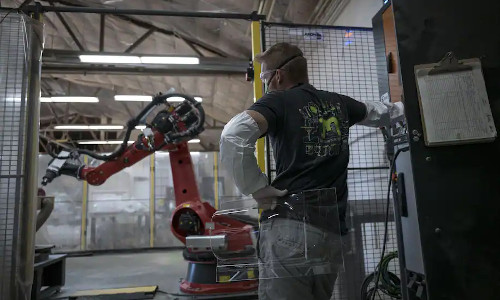 A worker watches a robot cut a piece of plastic for a face shield at Mask and Shield.